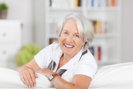 Portrait of a beautiful senior woman relaxing on a sofa leaning over the back of the cushion looking at the camera with a lovely smile photo