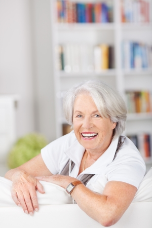 contented: Senior woman unwinding on a sofa in her living room smiling with enjoyment as she leans over the back of the furniture Stock Photo