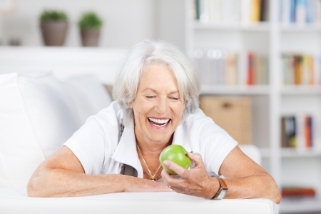 Happy senior woman holding an apple while lying on sofa at home photo