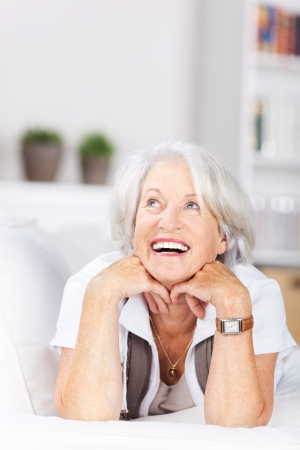 ascending: Laughing senior woman lying on a sofa facing the camera with a beaming friendly smile looking up towards copyspace above her head