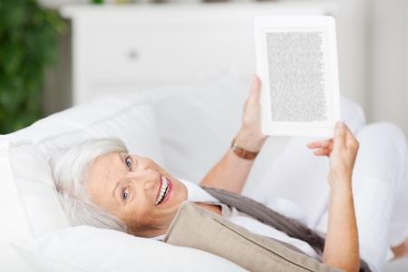 ソファの上に横たわっている間電子ブックを持って幸せな年配の女性の肖像画
