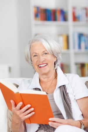 Portrait of happy senior woman holding book while sitting on sofa photo