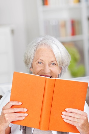 large woman: Smiling older woman hiding behind her large orange hardcover book which she is holding up in front of her so that just her eyes are visible Stock Photo