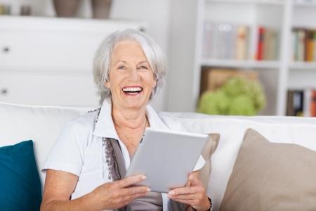 カメラを見て笑っている美しい年配の女性の自宅でソファに座って彼女の手でタブレット pc