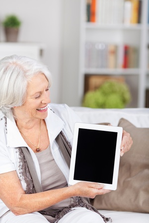 Smiling elderly woman sitting on a sofa in her living room at home showing off her tablet-pc holding the blank screen towards the camera photo