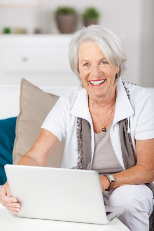 silver surfer: Portrait of happy senior woman using laptop while sitting on sofa