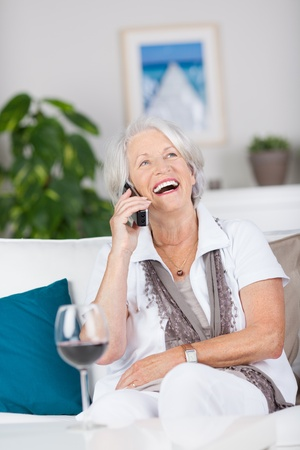 cordless: Happy senior woman conversing on cordless phone while sitting on sofa at home