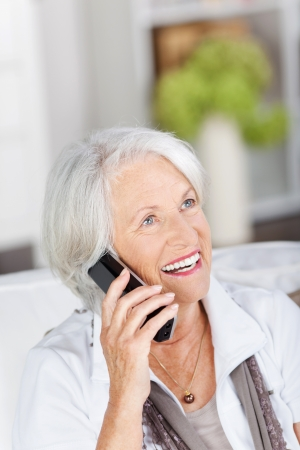 Vivacious beautiful senior woman on the telephone holding the wireless handset to her ear while relaxing in her living room at home Stock Photo - 21341306