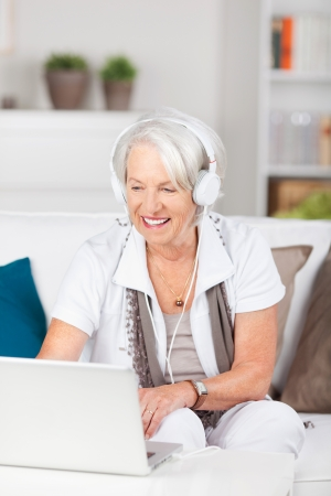 Happy senior woman wearing headset while using laptop on sofa at home photo