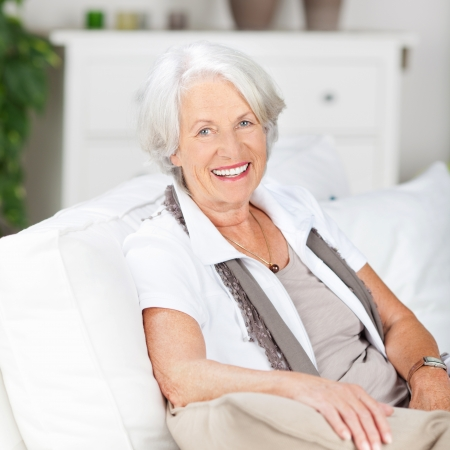 one senior adult woman: Friendly senior woman with a beautiful smile relaxing at home on a sofa in her living room