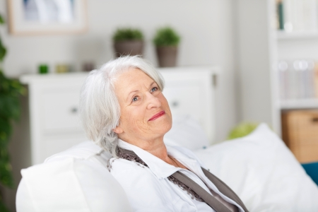 fond: Daydreaming smiling elderly woman relaxing on a sofa in her living room smiling as she recalls fond memories Stock Photo