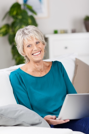 Portrait of happy senior woman using laptop while sitting on sofa at home photo