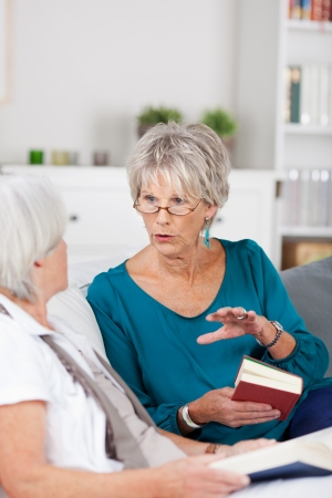 friendship women: Two senior women having a conversation as they sit together on a sofa in the living room reading their books Stock Photo