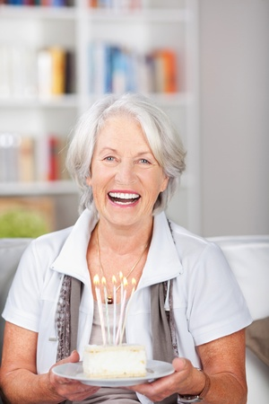 Laughing elderly woman holding a birthday cake with burning candles as she sits on a couch in her living room celebrating her birthday