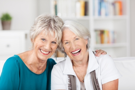 Portrait of happy female senior friends sitting on sofa