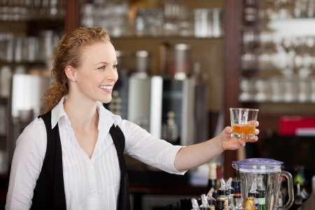 Smiling beautiful young barmaid serving alcohol in a tumbler to a client across the top of the bar counter photo