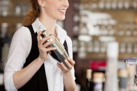 shaker: Barmaid shaking a cocktail shaker as she stands behind the bar mixing a drink for a client