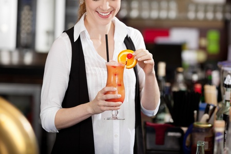 Female bartender making a tropical fruit cocktail holding an elegant long glass of beverage in her hand as she adds the sliced orange garnish to the rim Stock Photo - 21375161