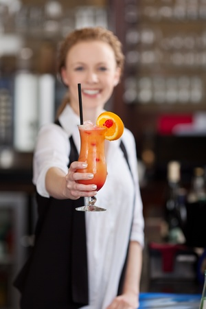 Smiling barmaid holding out a tropical fruit cocktail made with orange juice and rum photo