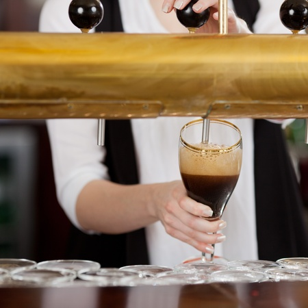 Waitress pouring a pint glass of dark beer from the automated keg behind the bar photo