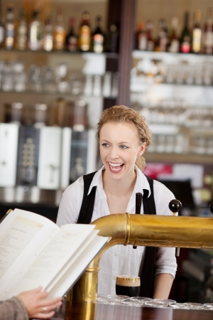 Laughing beautiful vivacious young barmaid serving drinks behind a bar counter in a pub or restaurant