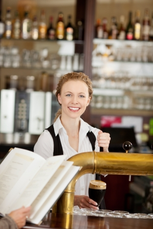 Smiling beautiful young barmaid standing behingd the counter in a pub or restaurant serving dark draft beer photo