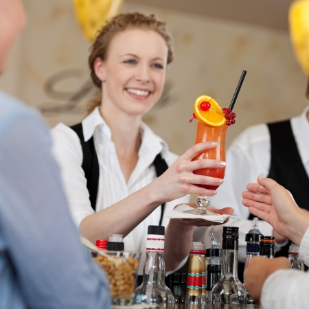 20s waitress: Guest being served a colourful orange and rum tropical cocktail by a smiling barmaid in a hotel or restaurant Stock Photo