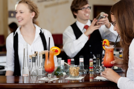 Two bartenders, a man and beautiful smiling young woman, mixing cocktails at the bar photo
