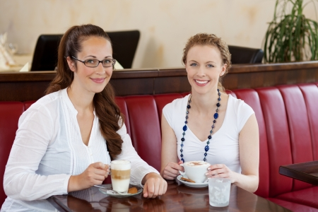 Two beautiful women in a cafe sitting at a table together drinking cappuccino coffee and macchiato photo