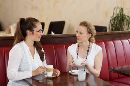 Two stylish beautiful young female friends sitting chatting in a cafe while enjoying cups of coffee Stock Photo - 21375177