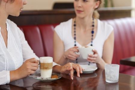 amigas conversando: Recorta la vista de cerca de dos mujeres jóvenes de tomar café en un restaurante o cafetería