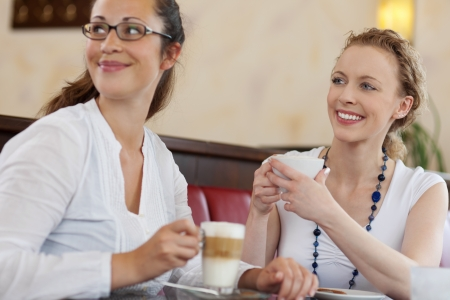 Two attractive young female friends enjoying themselves over coffee in a cafe looking to the side as they laugh and smile photo