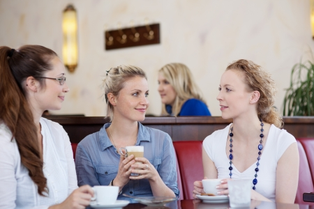 Three attractive stylish young female friends drinking coffee together and chatting in a cafe Stock Photo - 21375203