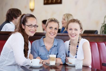 socializando: Feliz tres j�venes amigas goza de una taza de caf� en una cafeter�a