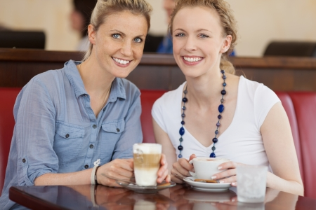 Two beautiful happy female friends enjoying a cup of cofee at a cafeteria photo