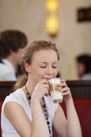 Young woman daydreaming while drinking a late macchiato in a cafeteria Stock Photo - 21375204