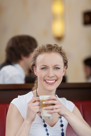 Portrait of a happy young woman enjoying a cup of late macchiato, in a cafeteria Stock Photo - 21375205