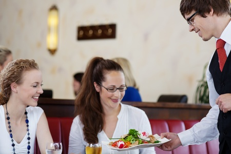 Friendly waiter serving a salad platter to two attractive young women friends sitting together enjoying a meal in a restaurant photo