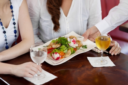 Waiter serving a plate of salad to a woman guest in a restaurant, cropped close up view of the food and his hand photo