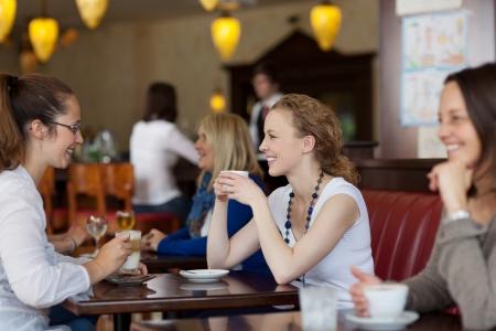 お客様のテーブルで一緒に座っている 2 つのスタイリッシュな若い女性にフォーカスを持つレストランでコーヒーを楽しむ