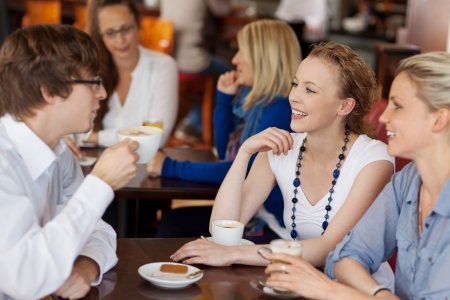 Three young friends having coffee together in a cafe seated around a small table chatting and smiling photo