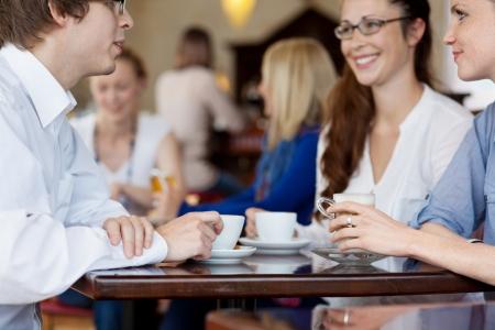 socializando: Jóvenes amigos disfrutando de una taza de café en una cafetería, un disparo desde un ángulo bajo