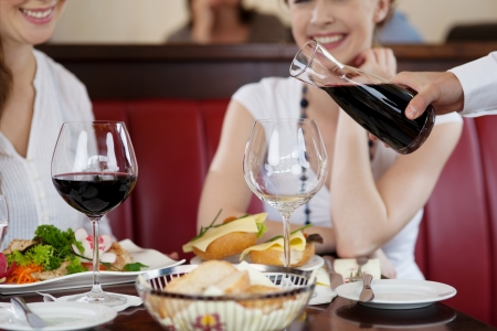 Waiter pouring red wine from a carafe at a restaurant for two young women seated at a table with their food Stock Photo - 21375214