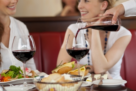 Two women enjoying red wine sitting eating a meal in a restaurant and chatting while the waiter replenishes their glasses Stock Photo - 21375215