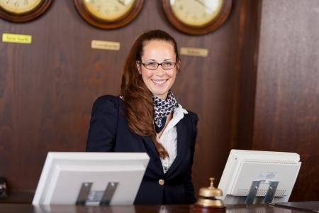 recepcionista: Amable recepcionista hermosa joven con estilo de pie detr�s de un mostrador en un vest�bulo con una sonrisa de bienvenida Foto de archivo