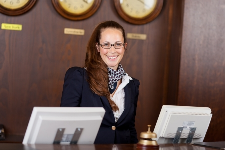 Friendly beautiful stylish young receptionist standing behind a counter in a hotel lobby with a welcoming smile photo