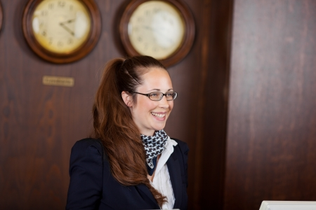 Young Caucasian friendly woman working at the reception of a hotel, with clocks in the background Stock Photo - 21375219