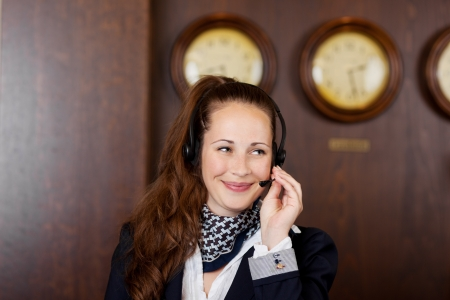 Friendly receptionist wearing a headset listening to a call while giving a beautiful smile Stock Photo - 21375225