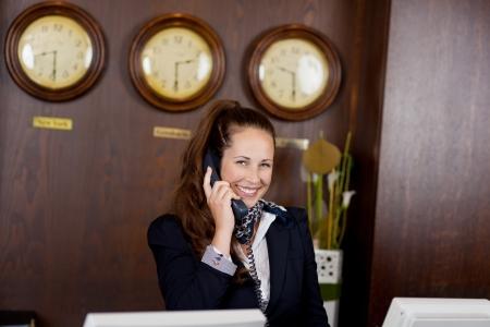 Gelukkig stijlvolle jonge receptionist praten over een telefoon die achter een balie in een hotellobby of internationale locatie met prikklokken boven haar hoofd Stockfoto