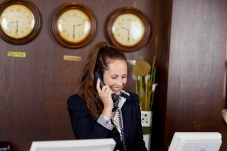 recepcionista: Recepcionista sonriente de tomar una llamada telefónica mientras está de pie detrás del mostrador en el vestíbulo de un hotel o lugar de celebración corporativa